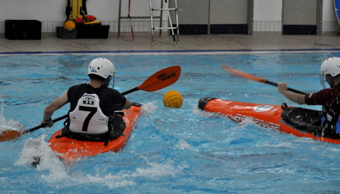 Canoe polo players chase the ball